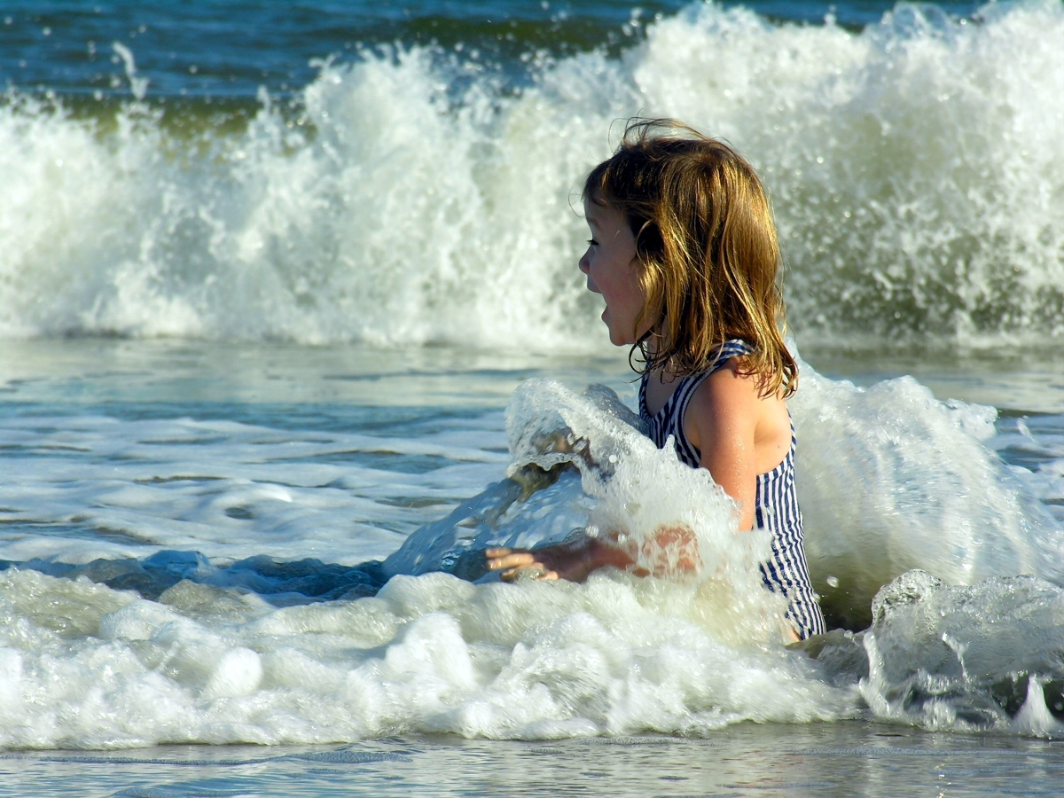 Girl playing in the beachfront ocean waves