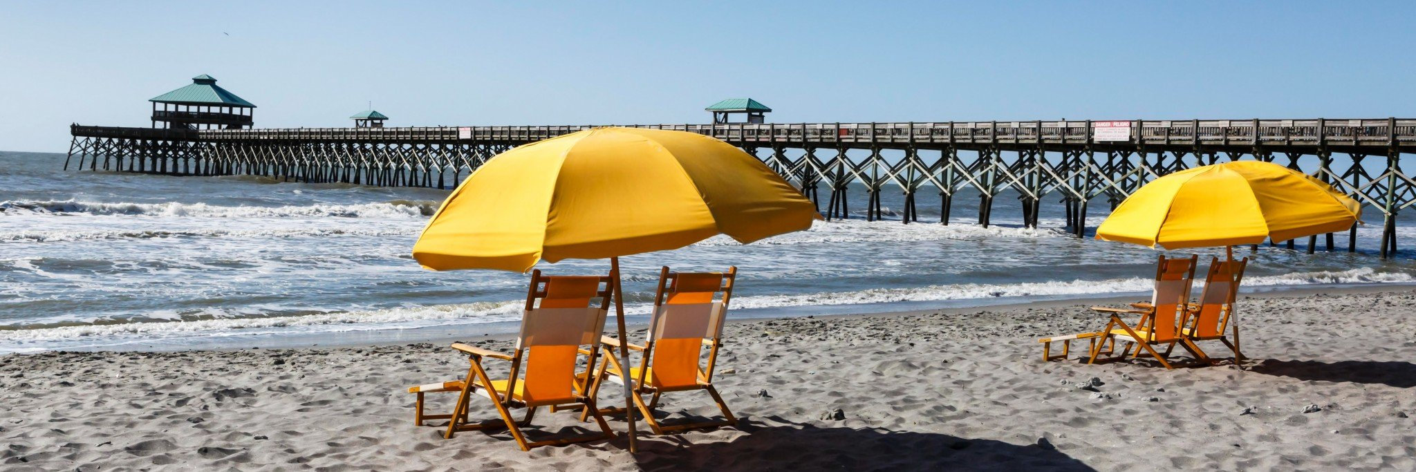 folly beach pier with yellow umbrella